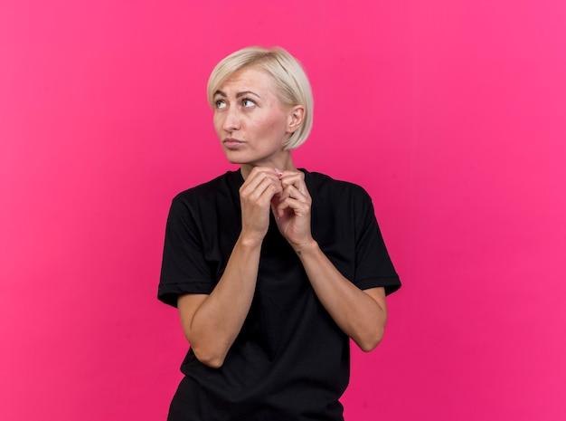 Mulher eslava loira de meia-idade pensativa, de mãos dadas, olhando para o lado isolado em um fundo carmesim com espaço de cópia