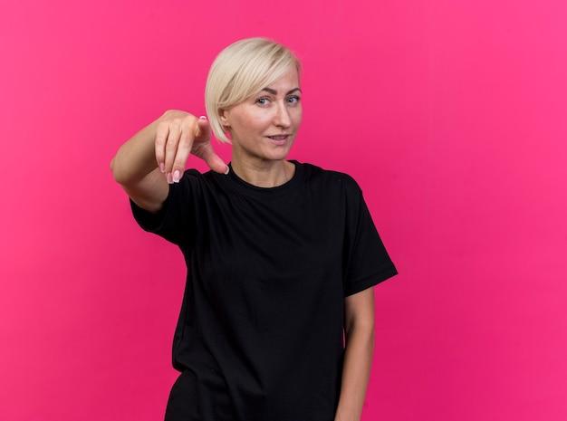 Mulher eslava loira de meia-idade satisfeita olhando e apontando para a câmera isolada em um fundo carmesim com espaço de cópia