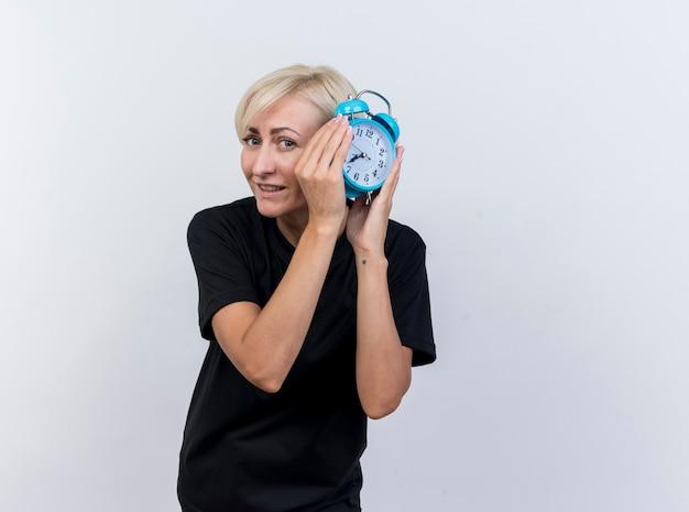 Mulher eslava loira de meia-idade satisfeita olhando para a câmera segurando o despertador perto da cabeça, isolado no fundo branco com espaço de cópia