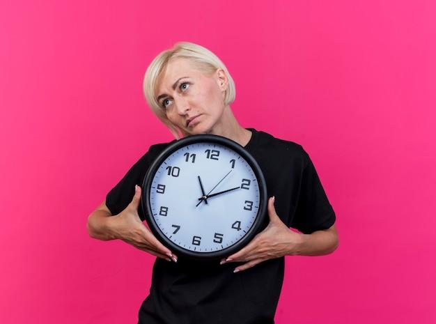 Mulher eslava loira de meia-idade segurando um relógio olhando para o lado isolado na parede carmesim