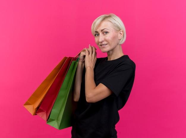 Mulher eslava loira de meia-idade sorridente em vista de perfil, segurando sacolas de compras, olhando para a câmera isolada em um fundo carmesim com espaço de cópia