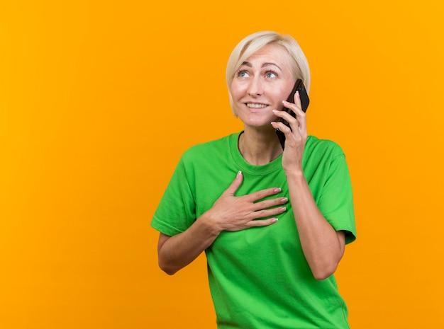 Mulher eslava loira de meia-idade sorridente falando ao telefone, mantendo a mão no peito, olhando para o lado isolado na parede amarela com espaço de cópia