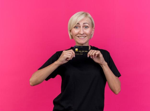 Mulher eslava loira de meia-idade sorridente, olhando para a câmera mostrando um cartão de crédito isolado em um fundo carmesim