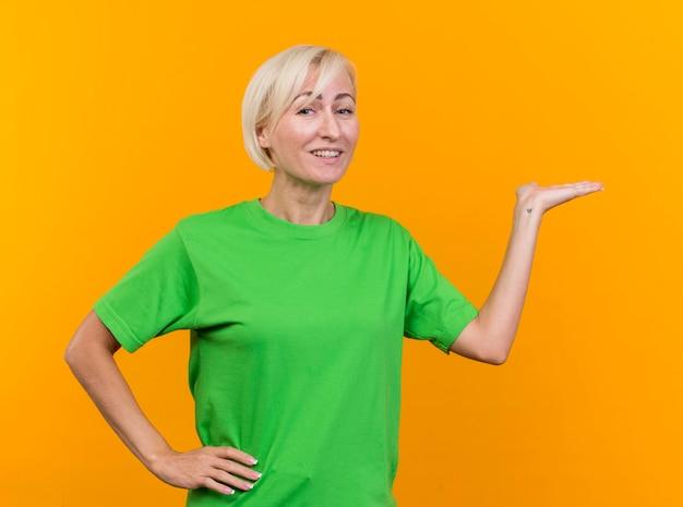 Mulher eslava loira de meia-idade sorridente, olhando para a frente, mantendo a mão na cintura apontando com a outra mão ao lado isolada na parede amarela
