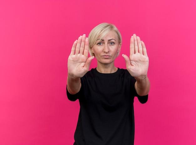 Mulher eslava loira rígida de meia-idade fazendo gesto de parada isolada na parede carmesim com espaço de cópia