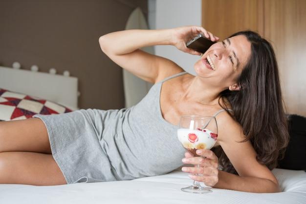 Mulher espanhola morena atraente de meia idade posando com um copo de sorvete com frutas