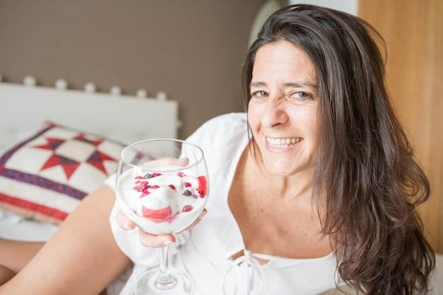 Mulher espanhola morena atraente de meia-idade posando com um copo de sorvete com frutas
