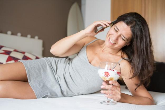 Mulher espanhola morena atraente de meia idade posando com um sorvete enquanto fala na foto