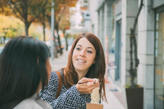 Mulher espanhola ouvindo a amiga na rua enquanto toma comida asiática