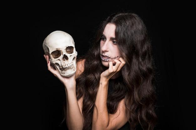 Mulher espantada a olhar para o crânio