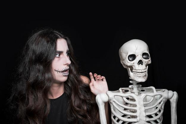 Mulher espantada a olhar para o esqueleto