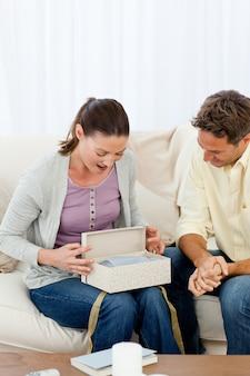 Mulher espantada abrindo um presente de seu namorado no sofá