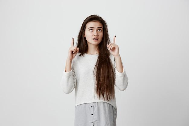 Mulher espantada com cabelos escuros longos e lisos, vestindo roupas casuais, olhando com olhos escuros para cima e boca amplamente aberta, apontando com os dedos indicadores no espaço da cópia