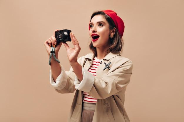 Mulher espantada com roupa segura a câmera no pano de fundo isolado. linda garota na boina vermelha brilhante faz foto em fundo bege.