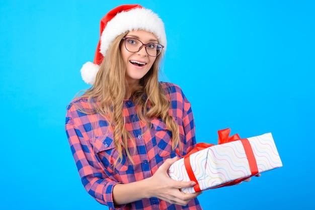 Mulher espantada com um presente de natal nas mãos