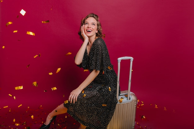 Mulher espantada com vestido longo pontilhado olhando confetes brilhantes na festa de boas-vindas