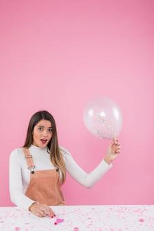 Mulher espantada em pé com balão de ar