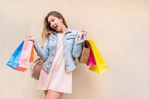 Mulher espantada, em pé com sacos de compras na parede