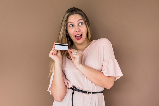 Mulher espantada em vestido de pé com cartão de crédito