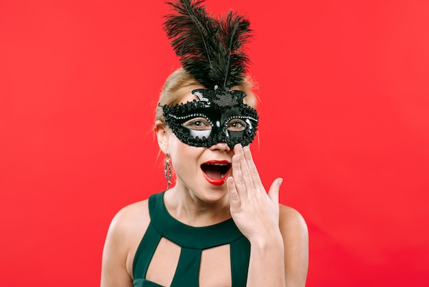 Mulher espantada na máscara de carnaval preto