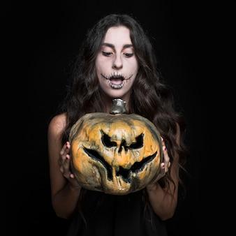 Mulher espantada segurando a abóbora de halloween