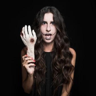 Mulher espantada, segurando a mão morta