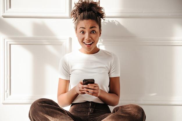 Mulher espantada segurando um smartphone