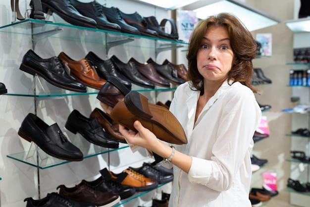 Mulher espantada segurar dois pares de sapatos masculinos.