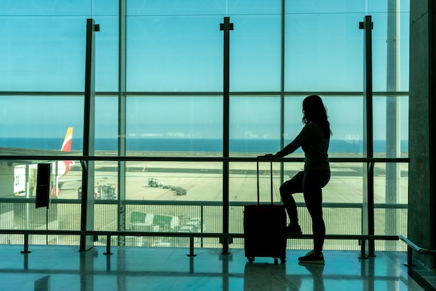 Mulher esperando avião no terminal do aeroporto usando smartphone - fuerteventura - espanha