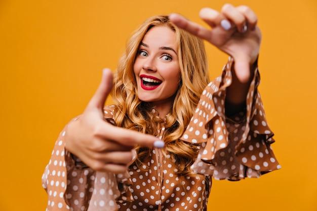 Mulher espetacular de olhos azuis posando na parede amarela. foto interna de uma garota elegante brincando durante a sessão de fotos.
