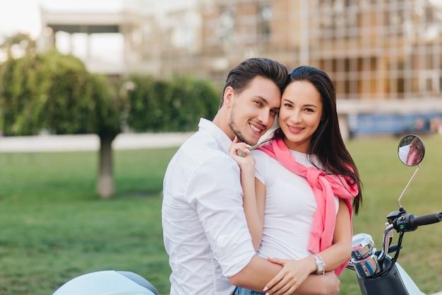 Mulher espetacular em pulseira de prata acariciando suavemente o marido, posando com ele em um quadrado