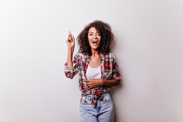 Mulher espetacular em trajes elegantes expressando entusiasmo. retrato de jovem alegre em pé de camisa quadriculada em branco.