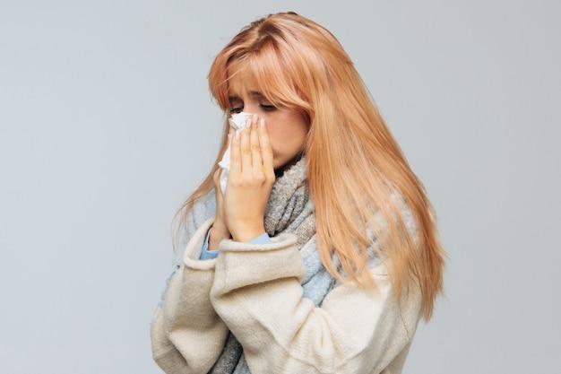 Mulher espirros, usando guardanapo. rinite, alergia, gripe