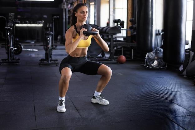 Mulher esporte com kettlebell no ginásio.