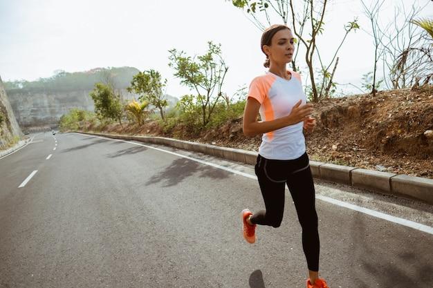 Mulher esporte correndo no lado da estrada