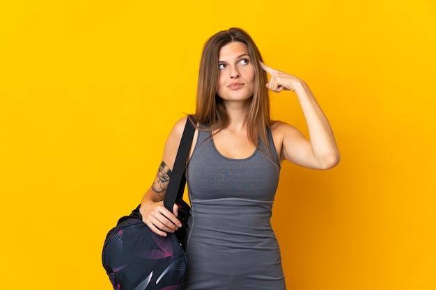 Mulher esporte eslovaca com bolsa esporte isolada em fundo amarelo, tendo dúvidas e pensando