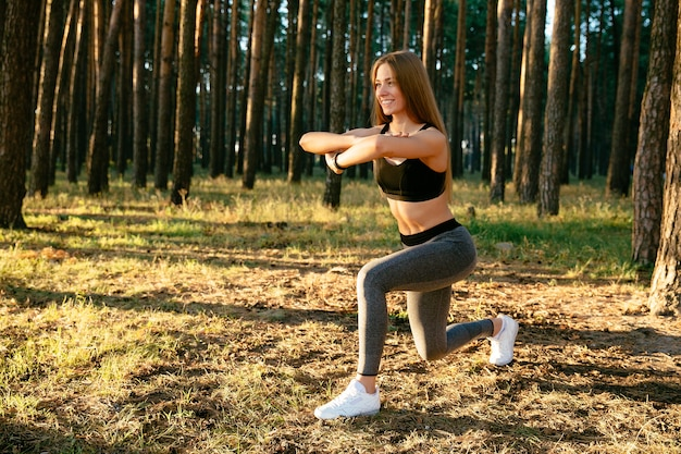Mulher esportiva alegre na parte superior do tanque e leggings, fazendo alongamento para o corpo