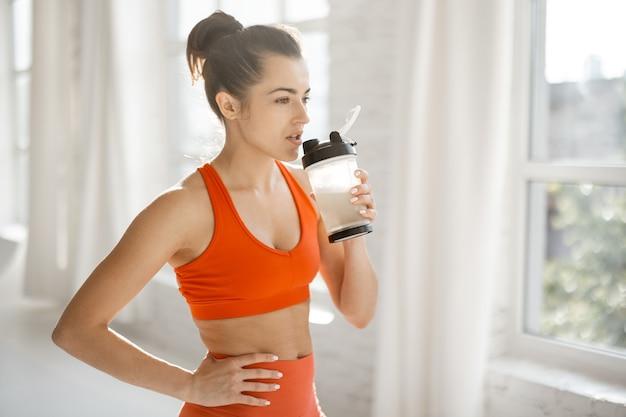 Mulher esportiva com agitador de proteína na academia