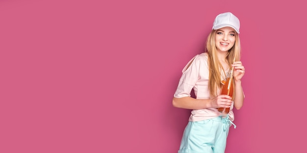 Mulher esportiva com bebida gelada em pé na parede rosa