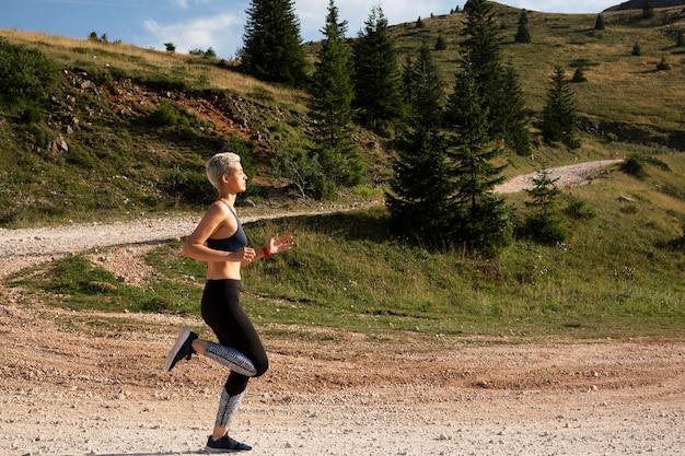 Mulher esportiva com cabelo curto correndo na natureza