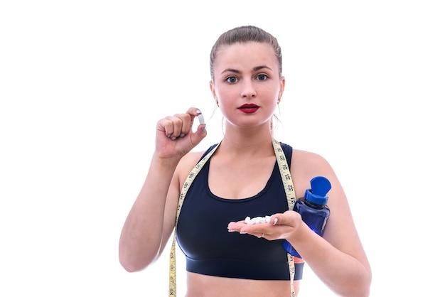 Mulher esportiva com comprimidos e frasco isolado no branco