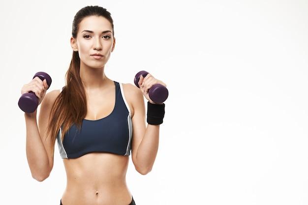 Mulher esportiva com halteres no sportswear posando em branco.