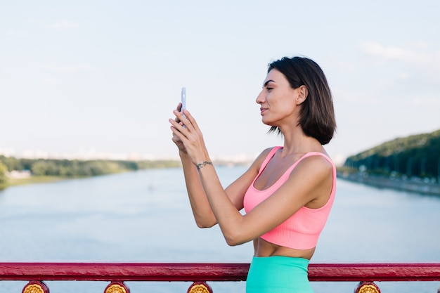 Mulher esportiva com roupas esportivas adequadas ao pôr do sol na ponte moderna com vista para o rio feliz sorriso positivo com telefone celular