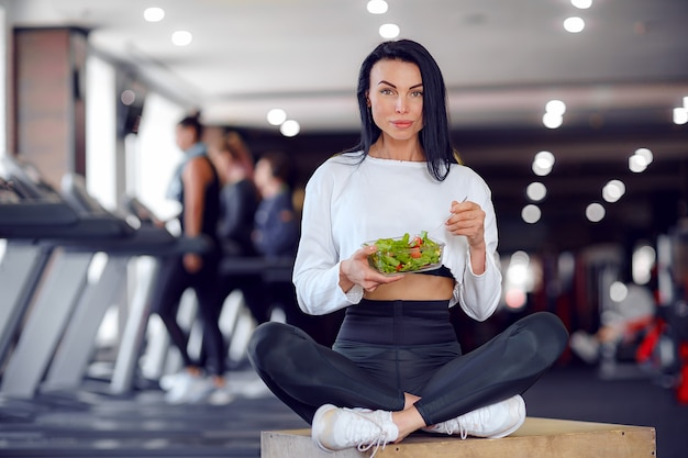 Mulher esportiva comendo salada