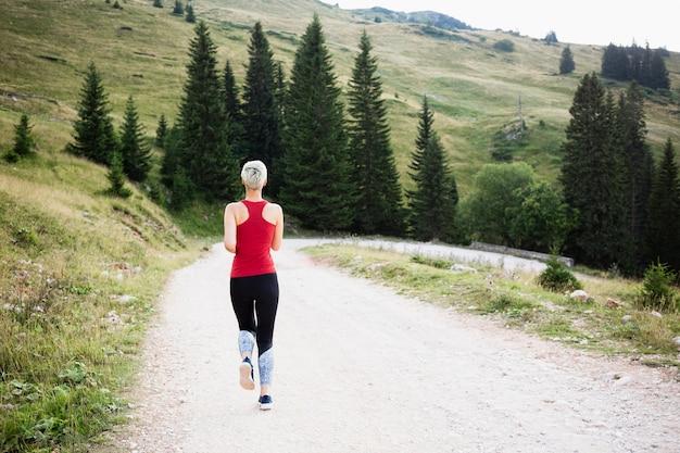 Mulher esportiva correndo na natureza