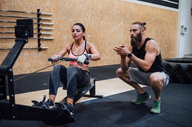 Mulher esportiva cruz apto remo de treinamento na máquina de remador com personal trainer
