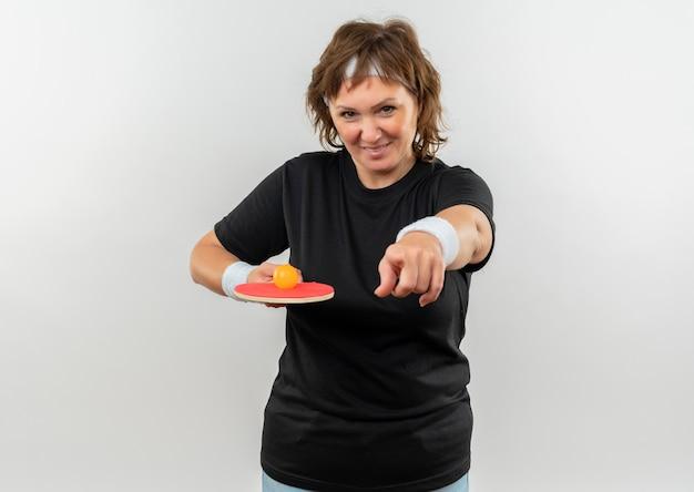 Mulher esportiva de meia-idade em camiseta preta com bandana segurando a raquete com bola para tênis de mesa apontando com o dedo para a câmera e sorrindo com uma cara feliz em pé sobre a parede branca