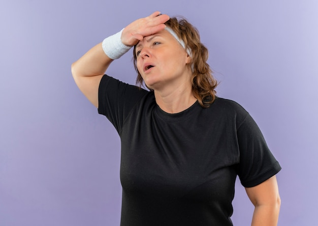 Mulher esportiva de meia-idade em uma camiseta preta com bandana olhando para o lado com a mão na cabeça cansada e exausta após o treino em pé sobre a parede azul