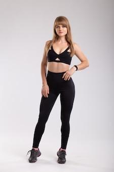 Mulher esportiva em caneleiras pretas e top preto