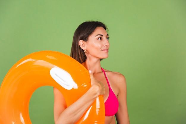 Mulher esportiva em forma de verão em biquíni rosa e anel inflável laranja brilhante redondo em verde, feliz alegre animado alegre positivo